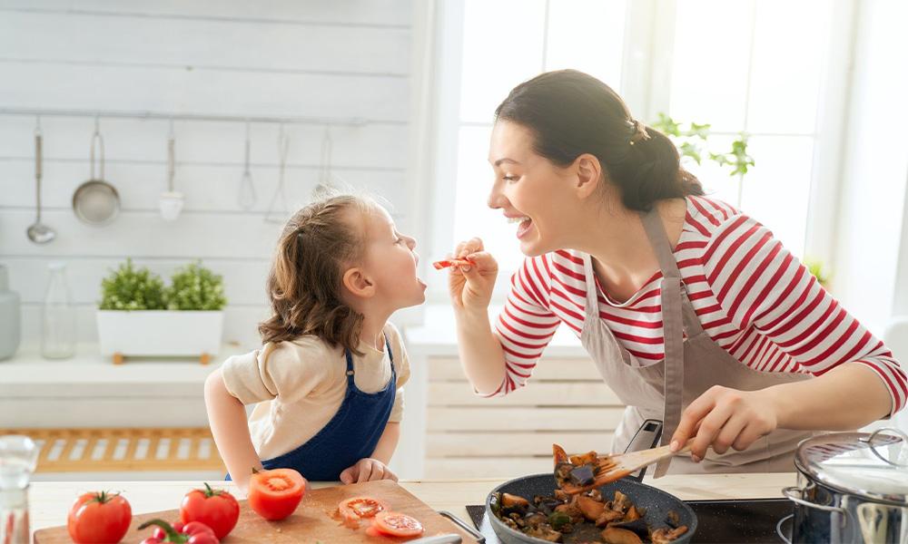 Mãe cozinhando com a filha