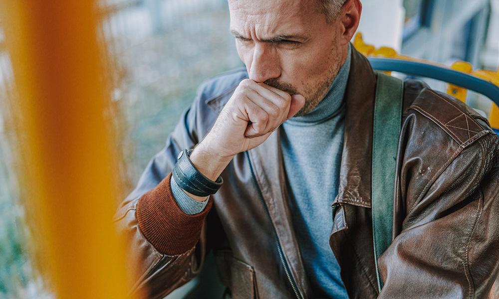 Homem tossindo no ônibus