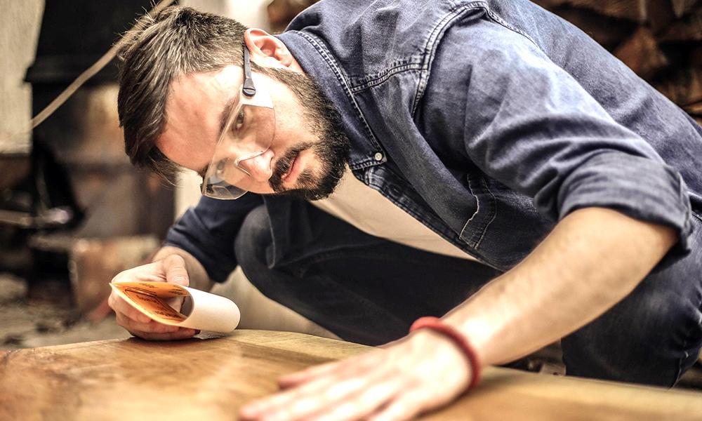 Homem com lixa na mão para reformar móveis