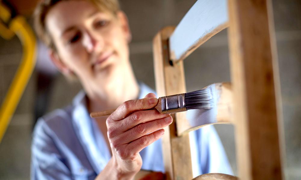 Mulher com pincel pintando a cadeira