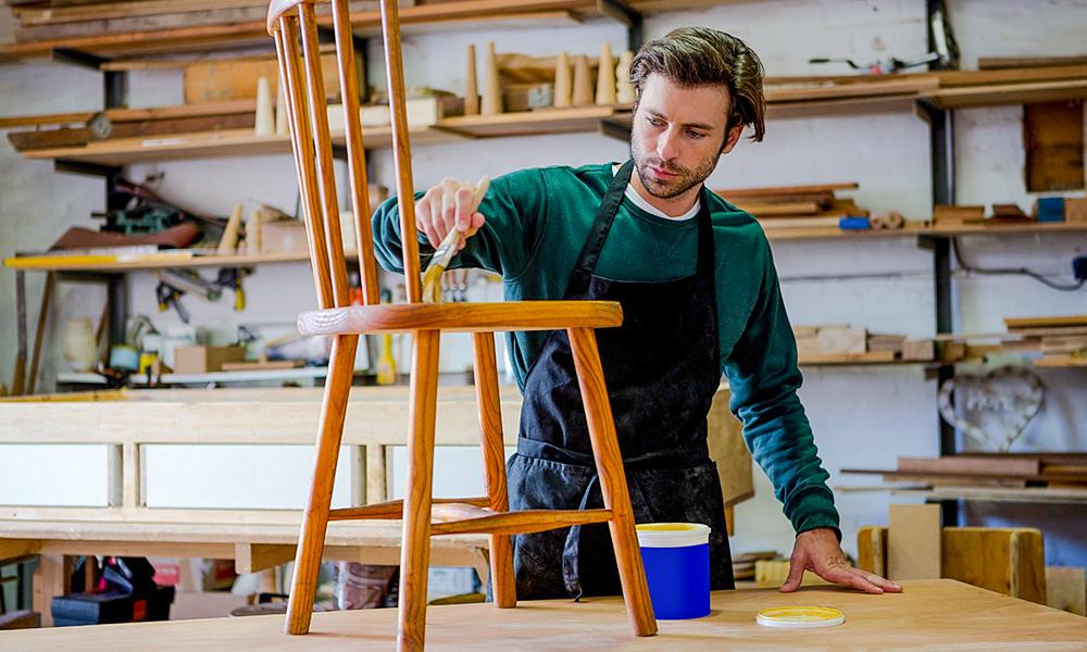 Homem com pincel pintando cadeira